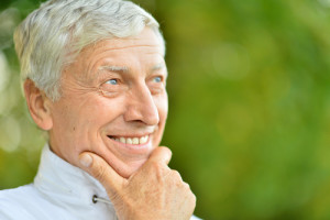 Older Man Smiles and Thinks About the Benefits of Dental Implants